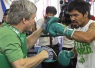 Manny Pacquiao, of the Philippines, spars with his trainer Freddie Roach at a media workout in preparation for his upcoming boxing match against Timothy Bradley, at Roach's Wild Card Boxing Club in Los Angeles Wednesday, May 30, 2012. Pacquiao will be defending his World Boxing Organization (WBO) welterweight championship crown against WBO junior welterweight champion Bradley at the MGM Grand Garden Arena in Las Vegas Saturday, June 9. (AP Photo/Reed Saxon)