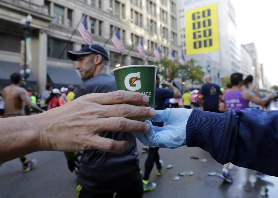 A runner grabs water at an aid station during the annual Chicago Marathon in Chicago, Sunday, Oct. 13, 2013. (AP Photo/Nam Y. Huh)