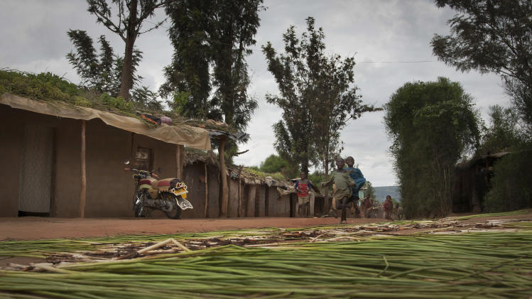 In this photo taken Tuesday, April 16, 2013, Rwandan refugee children run down a street in the Nakivale refugee camp in Uganda. Nearly two decades after the Rwandan genocide, thousands of refugees living in the camp in Uganda say they fear being forced to return to their home country. (AP Photo/Rebecca Vassie)