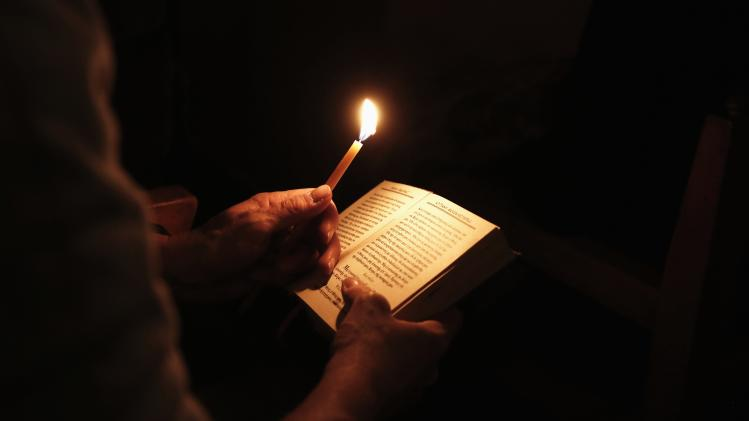 Orthodox faithful reads breviary book during mass of Holy Thursday inside church at Petraki monastery in Athens