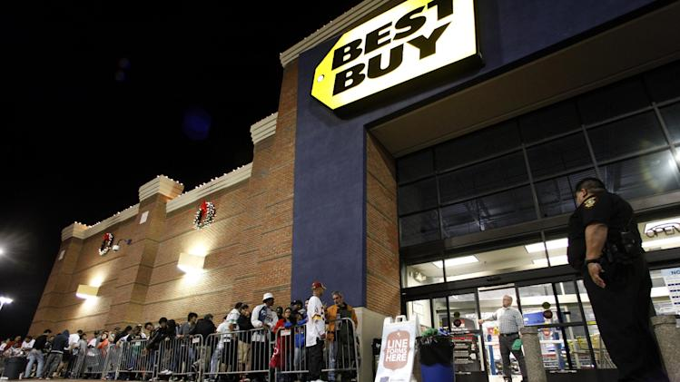 Tarrant County Sheriffs Deputy Nick Downs, right, watches a line of shoppers as Best Buy general manager Shaun Ogdie, standing at door, peers outside as he and his employees prepare to open at midnight Thursday Nov. 22, 2012, in Arlington, Texas. (AP Photo/Tony Gutierrez)
