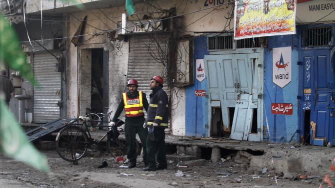 Pakistani rescuers collect remains at the site of a suicide bombing in Rawalpindi, Pakistan,Monday, Jan. 20, 2014. A Taliban suicide bomber blew himself up not far from Pakistan's military headquarters Monday, killing nine people a day after a militants bombing inside an army compound in the northwest of the country, officials and militants said. (AP Photo/Anjum Naveed)