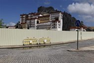 A building designed after the Potala Palace in Tibet and a fake volcano is seen behind a fence at Fisherman's Wharf in Macau July 28, 2013. REUTERS/Tyrone Siu