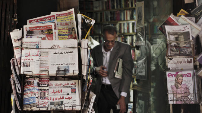 An Egyptian walks past a stand displaying  state-owned newspapers in Cairo, Egypt, Tuesday, Dec. 4, 2012. Most independent Egyptian newspapers suspended publication of Tuesday's edition in protest over the hurried drafting of the country's new constitution adopted by an Islamist-led panel. The media protest involved at least eight influential dailies and was part of a planned campaign of civil disobedience that could bring in other industries and build on an ongoing strike by Egypt's judges. (AP Photo/Nariman El-Mofty)