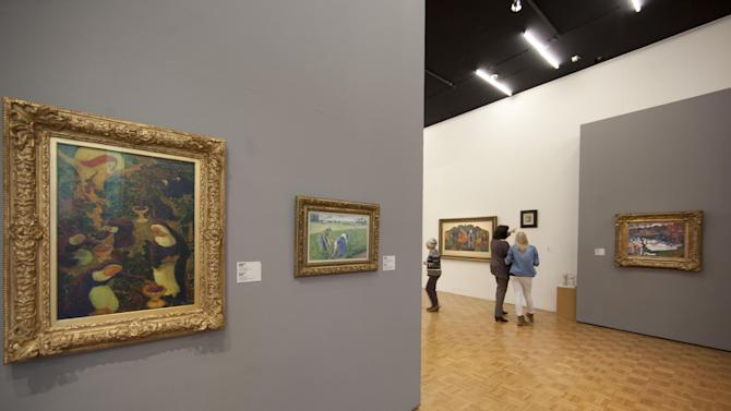 """Peasant Women Working in the Fields"" by Camille Pissarro, second painting from left, now hangs in place of the stolen Henri Matisse painting at Kunsthal museum, as the museum reopened its doors to the public following Tuesday morning's major art heist in Rotterdam, Wednesday Oct. 17, 2012. Police investigating a multimillion euro (dollar) art heist say they are following up several tips from the public, a day after thieves grabbed seven paintings from the walls of a Rotterdam gallery and vanished into the night. A spokeswoman for detectives on the case, Willemieke Romijn, said Wednesday they have some 15 tips from the public, following a late-night, nationally televised appeal for witnesses to the theft from the Kunsthal gallery of works by celebrated artists including Pablo Picasso, Claude Monet and Henri Matisse. (AP Photo/Peter Dejong)"