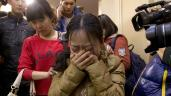 A Chinese relative of passengers aboard a missing Malaysia Airlines plane, center, cries as she is escorted by a woman while leaving a hotel room for relatives or