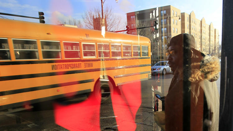 In this Monday, Dec. 3, 2012 photo, a man waits to cross 79th street as a school bus passes by in the Auburn-Gresham neighborhood on Chicago's South Side, seen in the reflection of a window. It's been a turbulent, bloody year in Chicago. A spike in murders and shootings, much of it gang-related, sent shock waves across the nation. Look closer and there are signs of distress and fear. Police cars watching kids board city buses at the end of the school day. Heavy security gates on barber shops and food marts. Thick partitions separating cash registers from customers. (AP Photo/Charles Rex Arbogast)