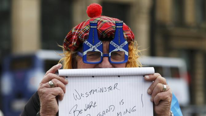 A supporter of the Scottish national Party holds upa sign at a rally in Glasgow