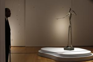 A guard stands beside Alberto Giacometti's life-size …