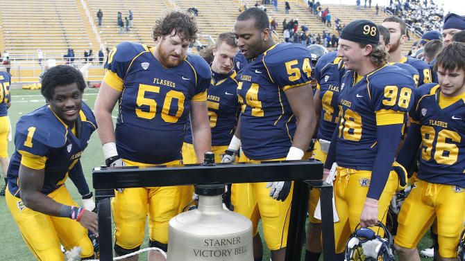 Kent State's Dri Archer (1) and teammates ring the victory bell after beating Ohio 28-6 in an NCAA college football game Friday, Nov. 23, 2012, in Kent, Ohio. (AP Photo/Ron Schwane)