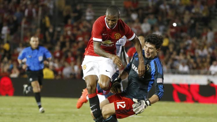 Manchester United midfielder Young challenges Los Angeles Galaxy's goalkeeper Rowe to score during the second half of their international soccer friendly match in Pasadena