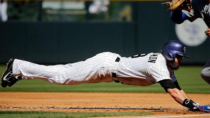 Colorado Rockies' Charlie Blackmon dives back to first to beat the tag during the first inning of a baseball game against the Los Angeles Dodgers, Wednesday, Sept. 17, 2014, in Denver. (AP Photo/Jack Dempsey)
