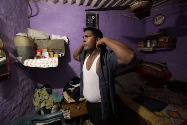 n this Monday, Aug. 20, 2012 photo, Pradeep Kumar puts on his security guard uniform as he gets ready to go to work at the Deen Dayal Upadhyay Hospital in New Delhi, India. Kumar and 20 other bouncers