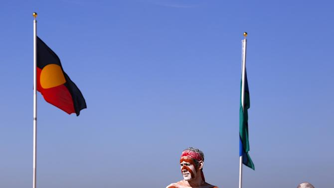 Traditionally dressed Australian Aboriginal performers stand next to an Aboriginal flag and a Toress Strait Islander flag on Sydney's Coogee Beach