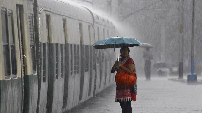 A woman holds an umbrella while waiting to board a train during a heavy rain shower at a railway station in Kolkata
