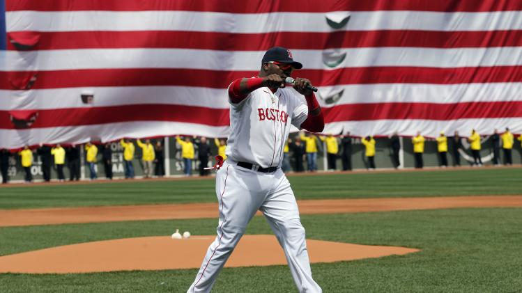 Boston Red Sox's David Ortiz pumps his fist in front of an American flag and a line of Boston Marathon volunteers, background, after addressing the crowd before a baseball game between the Boston Red Sox and the Kansas City Royals in Boston, Saturday, April 20, 2013. (AP Photo/Michael Dwyer)