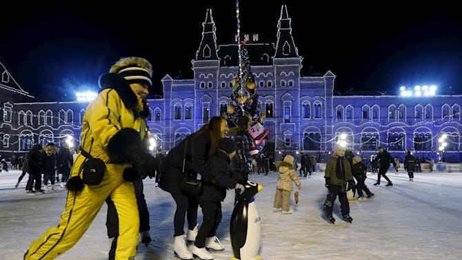 People skate at ice rink on its first day of operation in front of GUM department store in Moscow's Red Square