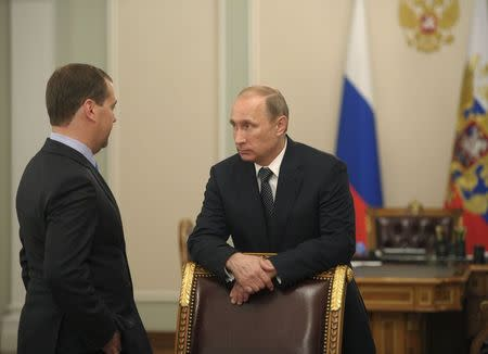 Russia's President Putin talks to Russia's Prime Minister Medvedev before a meeting on economic issues at Novo-Ogaryovo state residence outside Moscow