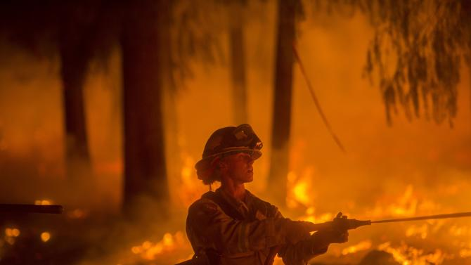 A firefighter battling the King Fire sprays water on a backfire in Fresh Pond, California