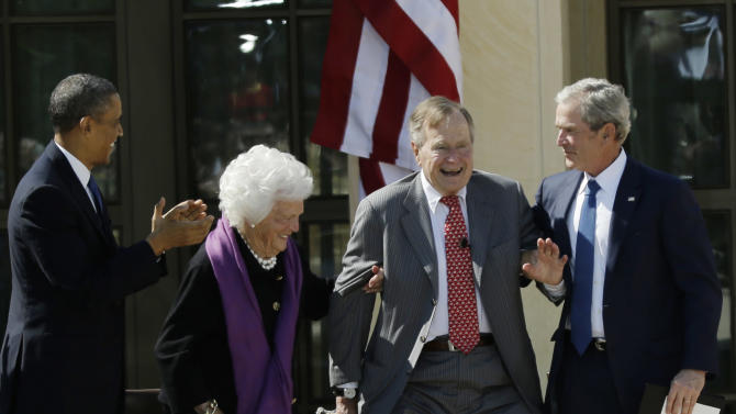 FILE - In this April 25, 2013, file photo President Barack Obama, left, applauds, as former first lady Barbara Bush, second from left, and former President George W. Bush right, help former President George H.W. Bush stand to acknowledge a standing ovation during the dedication of the George W. Bush Presidential Center in Dallas. The first President Bush is coming to the White House on Monday, July 15, 2013, for a ceremony Obama is holding to recognize the 5,000th Daily Point of Light Award, which Bush created more than two decades ago while in office to honor volunteer service. (AP Photo/David J. Phillip, File)
