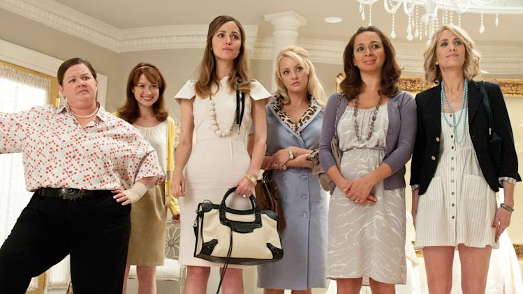 """In this publicity image provided by Universal Pictures, from left, Melissa McCarthy, Ellie Kemper, Rose Byrne, Wendi McLendon-Covey, Maya Rudolph and Kristen Wiig are shown in a scene from """"Bridesmaids.""""  """"Bridesmaids"""" and """"The Hunger Games"""" are battling for the most buckets of golden popcorn at the MTV Movie Awards. The raunchy comedy and survival saga are the top nominees at Sunday's 21st annual extravaganza with eight nods apiece. (AP Photo/Universal Pictures, Suzanne Hanover)"""