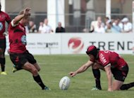 Toulon's Jonny Wilkinson (L) kicks a penalty assisted by teammate Matthew Giteau during the French Top 14 Rugby Union match against Racing Metro at the Yves du Manoir stadium in Colombes, outside Paris. Toulon fought back to beat Racing-Metro 23-21