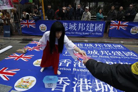 A protester in favor of Hong Kong as a city-state offers a placard to another protester during a march in Hong Kong