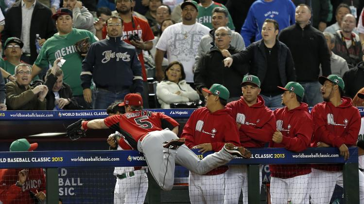 Canada's Taylor Green (5) reaches over the dugout rail but is unable toi catch a foul ball hit by Mexico's Ramiro Pena during the first inning of a World Baseball Classic baseball game, Saturday, March 9, 2013, in Phoenix. (AP Photo/Matt York)