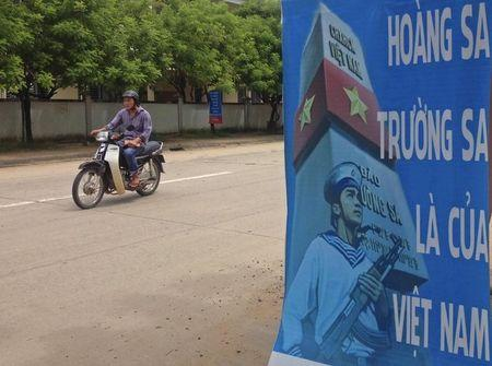 A man rides a motorcycle past a poster promoting Vietnam' sovereignty in the East Sea on Phu Quoc island