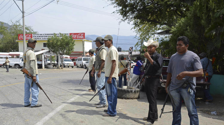 A group of armed vigilantes stand at the entrance to the town of Tierra Colorada, Mexico, Wednesday, March 27, 2013. Hundreds of armed vigilantes have taken control of this town on a major highway in the Pacific coast state of Guerrero, arresting local police officers and searching homes after a vigilante leader was killed. Several opened fire on a car of Mexican tourists headed to the beach for Easter week. (AP Photo/Bernandino Hernandez)
