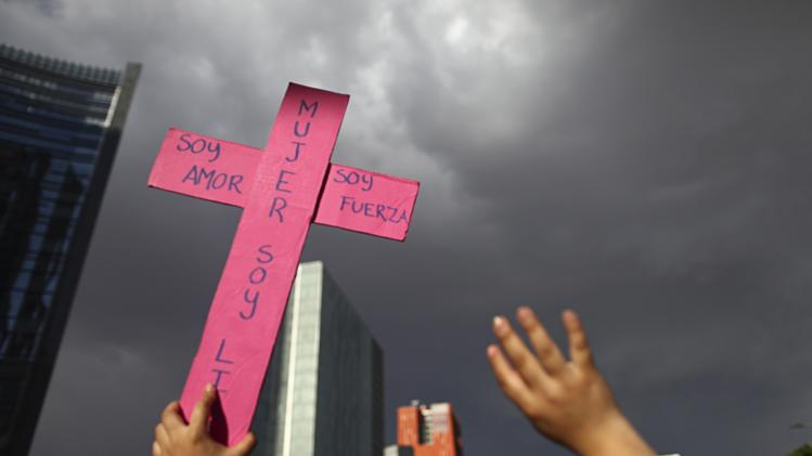 A woman holds up a cross during a march to mark International Women's Day in Mexico City