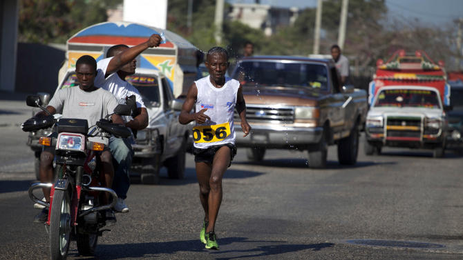 """In this Jan. 6, 2013 photo, Astrel Clovis, a 42-year-old marathon runner, competes in the """"Let's Go Haiti,"""" race, organized in honor of those who died in the 2010 earthquake,  Clovis has run the hills and streets of Port-au-Prince for the past 10 years. He decided to take the sport seriously after he entered a race in downtown Port-au-Prince on a whim - and won. In a country where good health is a luxury, running keeps Clovis strong. He clocks about 75 miles (120 kilometers) a week. (AP Photo/Dieu Nalio Chery)"""