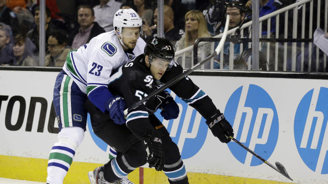 San Jose Sharks center Tommy Wingels, right, is covered by Vancouver Canucks defenseman Alexander Edler (23) is during the first period of Game 4 of their first-round NHL hockey Stanley Cup playoff series in San Jose, Calif., Tuesday, May 7, 2013. (AP Photo/Marcio Jose Sanchez)
