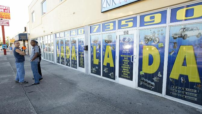 In this Feb. 12, 2013 photo, customers wait for a store that sells Russian auto parts, in Hialeah, Fla. to open. It's a niche market, but Fabian Zakharov has sold parts for hundreds of vintage Lada and Moskvitch cars that still fill the roads of the communist island. (AP Photo/J Pat Carter)
