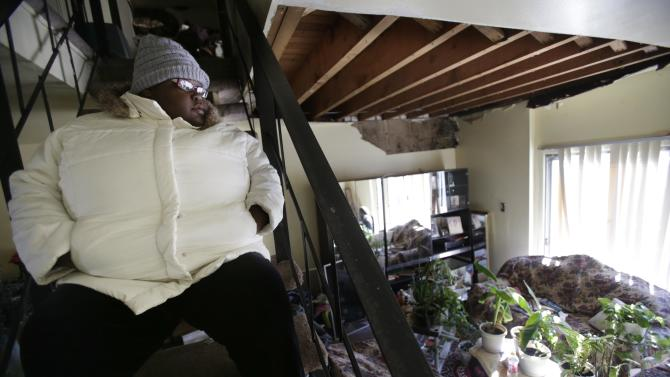 Ayanna Diego looks over her living room while waiting for inspectors at her home, which was damaged by Superstorm Sandy, in the Rockaways section of New York, Thursday, Jan. 24, 2013. Not only was the basement flooded, but water leaked through the roof and damaged the higher floors as well. (AP Photo/Seth Wenig)