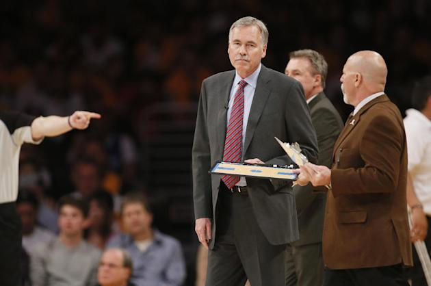 Los Angeles Lakers head coach Mike D'Antoni gets his clipboard from athletic trainer Gary Vitti during a time out against the Oklahoma City Thunder in the first half of an NBA basketball game in L
