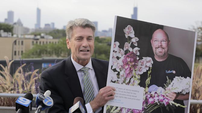 "Minneapolis Mayor R.T. Rybak, who recently married 46 same-sex couples following his state's passage of a law legalizing gay weddings, holds a advertisement as he appears at the Center on Halsted, in a predominantly gay neighborhood, Thursday, Sept. 5, 20136, , in Chicago. The mayor is visiting Chicago to launch a campaign called ""Marry Me in Minneapolis."" He plans to follow with campaigns in Colorado and Wisconsin, two other states that haven't approved same-sex marriage. Rybak is trying to convince Chicagoans that rather than take a long and expensive plane trip to one of the coasts, just drive six hours to his city. Recently, many gay couples in the Midwest have said their vows in Iowa, the only state directly bordering Illinois that allows same-sex weddings. (AP Photo/M. Spencer Green)"