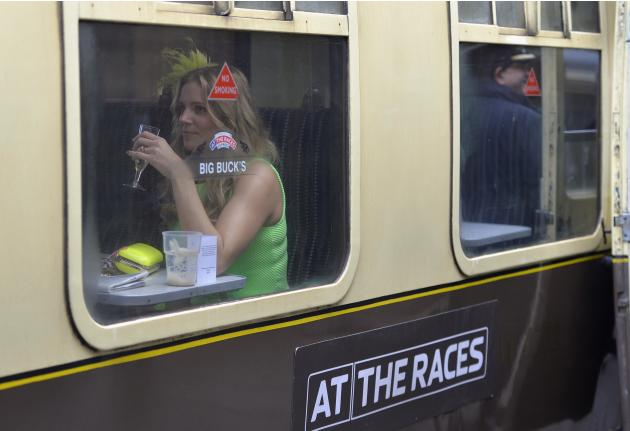 Racegoers arrive by train at the Cheltenham Festival horse racing meet in Gloucestershire, western England