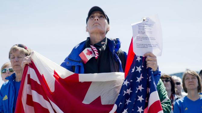 Ottawa runner Floralove Katz holds American and Canadian flags at Parliament Hill before a march to the United States Embassy in Ottowa in solidarity with the Boston community, in Ottawa on Monday, April 22, 2013. (AP Photo/The Canadian Press, Justin Tang)
