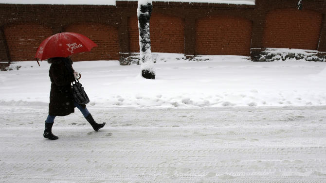 A woman walks through the snow covered street in Belgrade, Serbia, Sunday, Dec. 9, 2012. Freezing temperatures and heavy snowfall have killed at least 5 people and caused travel chaos across the Balkans. (AP Photo/Darko Vojinovic)