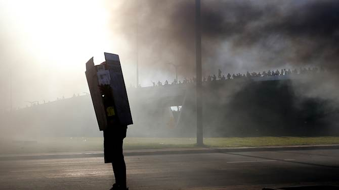 FILE - This June 19, 2013 photo, a protestor uses a cardboard box as a shield against rubber bullets during clashes with riot police near the Castelao stadium in Fortaleza, Brazil. Protesters cut off the main access road to the stadium where Brazil goes up against Mexico in the Confederations Cup soccer tournament. Beginning as protests against bus fare hikes, demonstrations have quickly ballooned to include broad middle-class outrage over the failure of governments to provide basic services and ensure public safety. (AP Photo/Andre Penner, File)