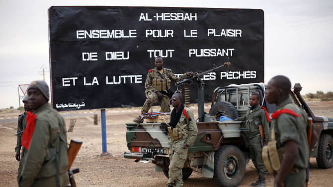 "Malian soldiers are stationed at the entrance of of Gao, Northern Mali, Monday Jan. 28, 2013. French and Malian troops held a strategic bridge and the airport in the northern town of Gao on Sunday as their force also pressed toward Timbuktu, another stronghold of Islamic extremists in northern Mali, officials said. The sign , a reminder of Islamic extremists, reads "" Al Hesbah, together for the pleasure of God almighty and the struggle against sins.""(AP Photo/Jerome Delay)"
