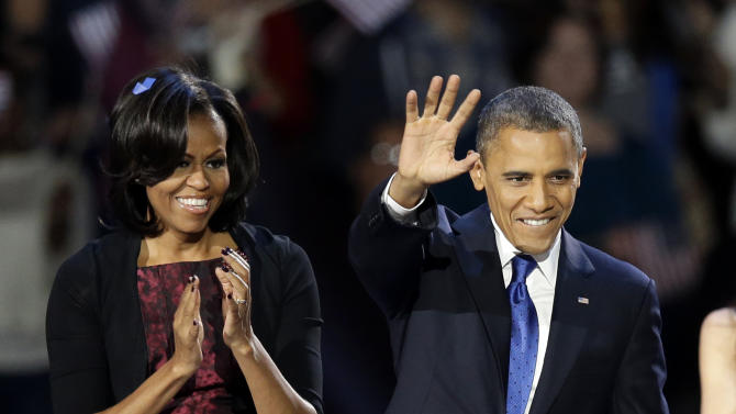 President Barack Obama and first lady Michelle Obama wave at his election night party Wednesday, Nov. 7, 2012, in Chicago. President Obama defeated Republican challenger former Massachusetts Gov. Mitt Romney. (AP Photo/Chris Carlson)