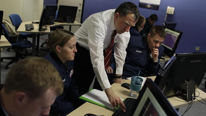 In this Feb. 20, 2013 photo, Martin Carlisle, standing, a computer science professor at the Air Force Academy and director of the school's Center for Cyberspace Research, instructs cadets in cyber warfare, at the U.S. Air Force Academy, in Colorado Springs, Colo. The U.S. service academies are ramping up efforts to groom a new breed of cyberspace warriors to confront increasing threats to the nation's military and civilian computer networks that control everything from electrical power grids to the banking system. (AP Photo/Brennan Linsley)