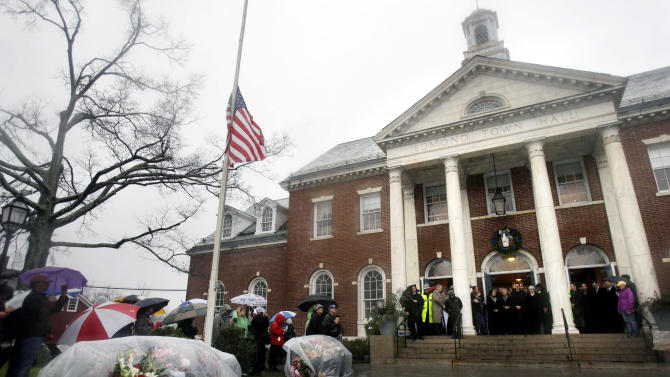 "FILE - In this Dec. 21, 2013 file photo, officials including Connecticut Governor Dan Malloy observe a moment of silence on the steps of Edmond Town Hall in Newtown, Conn., while bells ring 26 times for those killed a week earlier at Sandy Hook Elementary School. A comedy benefit event, ""Stand up for Newtown,"" is scheduled to be held at Town Hall on June 7, 2013. (AP Photo/Seth Wenig, File)"