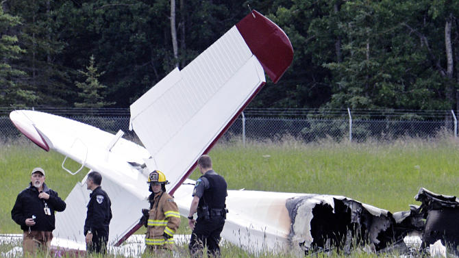 Police and emergency personnel stand near the remains of a fixed-wing aircraft that was engulfed in flames Sunday July 7, 2013 at the Soldotna Airport in Soldotna, Alaska. No survivors were located and it is unknown how many people were on board. (AP Photo/Peninsula Clarion, Rashah McChesney)