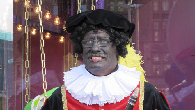 "In this photo taken Sunday, Nov. 18, 2012 a musician dressed as ""Zwarte Piet"" or ""Black Pete"" pauses during a parade after St. Nicholas, or Sinterklaas, arrived by boat in Amsterdam, Netherlands, Sunday, Nov. 18, 2012. Foreigners visiting the Netherlands in winter are often surprised to see that the Dutch version of St. Nicholas' little helpers resemble a racist caricature of a black person. The overwhelming majority of Dutch, who pride themselves on tolerance, are fiercely devoted to their holiday tradition and say ""Zwarte Piet"", whose name means ""Black Pete"", is absolutely harmless, a fictional figure who does not represent any race. But now a growing group of Dutch natives are questioning whether this particular part of the tradition should be changed. (AP Photo/ Margriet Faber)"