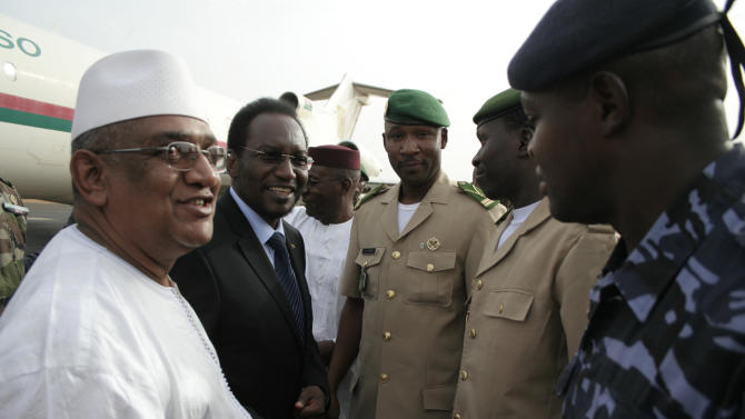 Dioncounda Traore, second left, Mali's parliamentary head who was forced into exile after last month's coup, is greeted by junta representatives including spokesman Lt. Amadou Konare, center, as Traore arrives at the airport to take up his constitutionally-mandated post as interim president, in Bamako, Mali Saturday, April 7, 2012. Traore's return comes after coup leader Capt. Amadou Haya Sanogo signed an accord late Friday agreeing to return the nation to constitutional rule. (AP Photo/Harouna Traore)