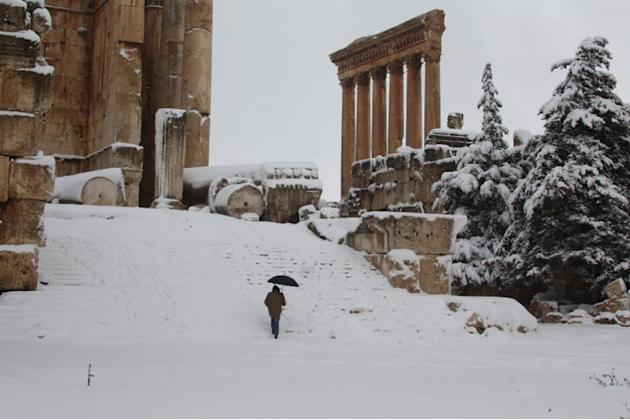 A visitor climbs the steps of Baalbek's Bachus temple as snow covers the Roman ruins of the historic town in eastern Lebanon's Bekaa Valley on January 9, 2013, following a fierce storm which has whipp