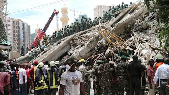 In this photo released by China's Xinhua News Agency, rescue workers search for survivors at the building collapse site in downtown Dar es Salaam, Tanzania, Friday, March 29, 2013. A Tanzanian police official says two people have died after a building under construction collapsed in the country's largest city and economic center. (AP Photo/Xinhua, Zhang Ping) NO SALES